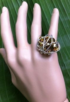 "This Silver filled wire and Gold Metallic color shades faceted beads knot ring is Unique and one-of-a-kind design.  Make sure to check my other rings in my ""hand jewelry"" category  Unicity jewels are unique, handmade with love by the designer. No two ítems are the same.  US size 4.75  Be Yourself, Be You-nique and Wear it Outloud!"