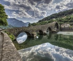 """The """"Devil's Bridge"""" got its name from an old Tuscan folk tale that describes it as having rare mystical powers. This beautiful stone bridge was constructed in the picturesque town of Cividale del Friuli during medieval times and spans a gorgeous river that crosses the town. This spectacular piece of masonry only shines brighter against a backdrop of the fantastic natural beauty in the surrounding area."""