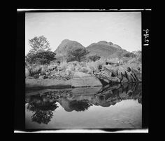 Waterhole at foot of Ruined Rampart, Petermann Ranges, Northern Territory 1926. The waterhole is in the image foreground. Its surface is still and mirror-like, reflecting the landscape and the sky. In the middle ground at the water's edge are numerous large rocks, some stacked next to each other like books. A large smooth rock in the image centre disappears into the water. Beyond the rocks is scrub with scattered trees and bushes. In the distance is a mountain range, with two ridges in front…