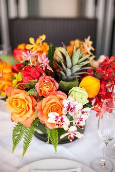 A tropical theme centerpiece of florals, fruit & greenery. Dillon Photography. See more..@intimatewedding #bouquet #tropicaltheme