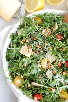 Lemon Arugula Salad with Pine Nuts is a quick and easy salad that is peppery, sweet and satisfying. Arugula is tossed with cherry tomatoes, toasted pine nuts and parmesan cheese and finished off with a lemony, olive oil dressing. // acedarspoon.com #salad #vegetarian