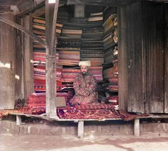 This is a market in Samarkand, he sells silk and wool fabrics together with some traditional middle east carpets. On the top of his trading place one can see a   page from Koran in the frame. 100 yr old photos restored.