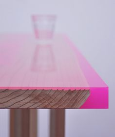japanese designer jo nagasaka from schemata architecture office has created a contemporary interpretation of the traditional japanese  hassoku dai, a low table with 8 legs, by using a plank as a table top that is then finished with a layer of colored epoxy resin in  fluorescent pink or yellow.