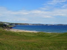 Picture of a bay with a sandy beach seen from dunes, a village with a harbour on the other side of the bay