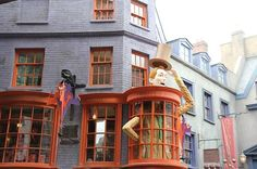 The Weasleys' Wizard Wheezes facade, which is bright and has a giant man standing through the window. | 19 Magical Finds At The Weasleys' Joke Shop In Universal's Diagon Alley
