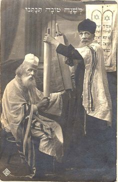 "Pictured here are two Jewish men in the synagogue following the Torah reading. The Hebrew greeting on top reads: ""May you be inscribed for a good year"" - Before the Holocaust"
