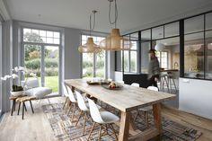Salle à manger familiale avec verrière noire dans une maison en Belgique totalement réaménagée par l'architecte d'intérieur Nancy Geernaert.
