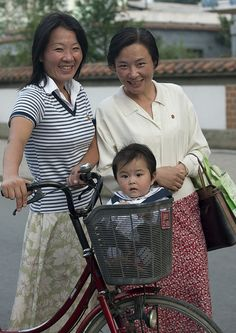 North Korean kid in a basket! Even though cars and gas is limited, many of the North Korean people get around in the capital via bike.