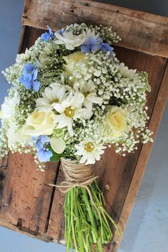 baby's breath, Queen Anne's Lace, Daisy, Cream Roses and hints of blue hydrangea. The blue hydrangea is exactly what I want.