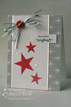 handmade Christmas card by Amy O'Neill ...gray and white with red accents ... like the design ... red stars with different prints ... splash of sequins ... red button on silver ribbon bow ... like it!! ... Stampin' Up!