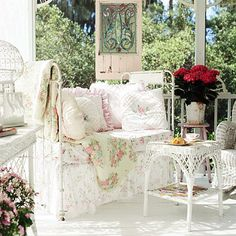 To create this look, a castaway crib was converted into a daybed. It is dressed in mini-floral fabrics. A stained-glass window subs for artwork./