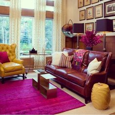Bold use of complementary colors: Merlot and Mustard Yellow seating with a Bright Purple rug. Beautifully complemented with wood and metallic accents.