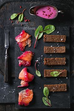 Salted Salmon with Toasts - Sliced salmon filet, salted with beetroot juice, served with whole wheat toasts, salad leaves, beetroot sauce and pink pepper over black slate surface. With vintage fork at left. Top view