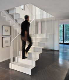 This delicate sculptural steel staircase is supported by vertical rods.