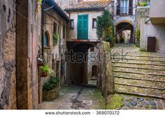 old traditional courtyard and alleyway in small medieval town of Sorano in Italy with potted plants