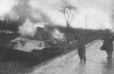 Un soldat américain  escorte un membre d'équipage allemand de son char Panther détruit durant la bataille de la crête de Elsenborn