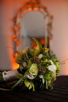 Orchids, scabiosa pods, succulents, berries, roses, lily grass, seeded eucalyptus and feather accents. Bridal bouquet at Top of the Town in Virginia.  Photo by Documentary Associates.  Flowers by Elegance and Simplicity!