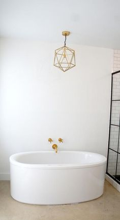 A gold polyhedron light pendant perfectly accents a brass wall mounted Kohler Purist Bathtub Faucet filling an oval freestanding tub by Kohler in this chic industrial bathroom. Farmhouse Bathtub Faucets, Bathroom Faucets, Bathtub Lighting, Kohler Purist, Wall Mount Tub Faucet, Stand Alone Tub, D House, Farm House, Taps