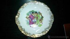 Plato decorativo de porcelana. Pintado a mano con pan de oro