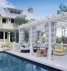 Poolside arbor draped in outdoor fabric with low, lounge-like patio furniture.