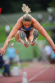 Female athlete in third phase of triple jump Royalty Free Stock Photo