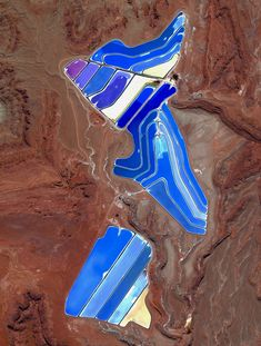 1/18/2017 Moab Evaporation Ponds Moab, Utah, USA 38·485579°, –109·684611°  Evaporation ponds are visible at the potash mine in Moab, Utah, USA. The mine produces muriate of potash, a potassium-containing salt that is a major component in fertilizers. The salt is pumped to the surface from underground brines and dried in massive solar ponds that vibrantly extend across the landscape. As the water evaporates over the course of 300 days, the salts crystallize out. The blue color seen here…