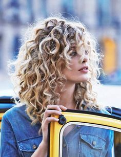 Medium length naturally curly hair with blonde highlights and face framing layers.