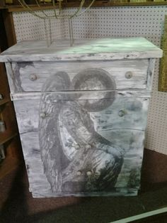 Greys and whites distressed dresser with angel on front. stone  knobs. @ rockin b's in sharpsburg, ga. 770-253-8730. vendor 103 Born in a Barn