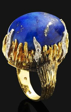 A lapis lazuli and diamond-set cocktail ring, 1960s The oval-shaped lapis lazuli cabochon mounted within a textured gold surround of flame motif, accented by brilliant-cut diamonds, to the textured hoop, mounted in 18 carat yellow gold, gross weight 21.5 grams, ring size K½