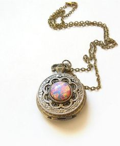 Pink Fire Opal Pocket watch Locket style Necklace This lovely necklace is made using a vintage glass fire opal . The opal is high quality and features flashes of pink, orange, yellow, and even green. The stone is circular in shape with a flat back and Art Deco Jewelry, Cute Jewelry, Vintage Jewelry, Jewelry Accessories, Antique Jewelry, Silver Jewelry, Jewelry Necklaces, Bling Bling, Do It Yourself Jewelry