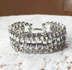 This beautiful find is for a cuff bracelet. It is signed Fenichel on the clasp. It is made of silver tone metal and features clear rhinestones that are bright, sparkling, and consistent. The clasp works securely. The bracelet is approximately 3/4 wide x 7 long including closed clasp.