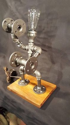 Pipe Lamp Art - Handmade lighted sculpture that is made from black industrial plumbing pipe. This acts as table lighting and shows your love for working out. Perfect for recreation rooms, man caves, or almost any place in the house. This lighted sculpture measures approximately 21 #LampArt