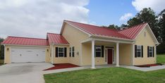 One story wheelchair accessible home exterior. Court yard garage. White columns. Red metal roof. Yellow exterior.