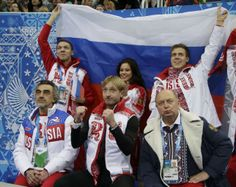 "Evgeny Plyushchenko of Russia and his team celebrate from the ""kiss and cry"" area during the Team Men Short Program at the Sochi 2014 Winter..."