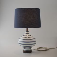 Defined by its simple curves, the Lafayette celebrates the classic lines and modern design reminiscent of early American lighting. The hand-blown glass base bears delicate stripes carefully handpainted on a wheel by artisans in West Virginia. Constructed in our Schoolhouse factory, the Lafayette is beautifully finished with a fabric drum shade, rich walnut neck and bottom and solid brass details.  Top-of-the-line dimmable socket. Includes 8 feet of twisted cloth cord and Bakelite plug.