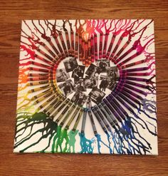 Hot glue crayons, onto a canvas, in the shape of a heart. Take a blow dryer to melt them. Place pictures of you guys inside the heart.
