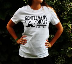 T-shirt in white.  Check out Gentlemen's Draft Clothing at https://www.facebook.com/GentlemensDraft   $2 from each item sold is donated to prostate cancer research.  Join us in  helping to fight cancer, one shirt at a time.  Stay classy like never before with our signature moustache and glasses logo on our custom designed threads.  Also check us out on:  Instagram - gentlemens_draft