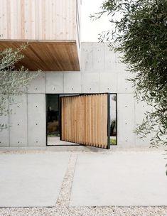 Betonnen woonhuis in combinatie met een houten volume. De grote houten poort in een zwart stalen frame geeft toegang tot het binnenterrein.