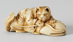 An ivory netsuke of a spotted cat on a namazu. Late 19th century, Auktion 1044 Asiatische Kunst, Lot 958