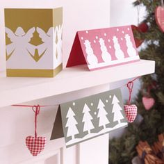Paper cut-out handmade Christmas cards on mantlepiece - personalised cards - craft - allaboutyou.com