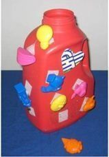 Velcro small toys to the outside of the bottle. Child removes them and inserts them into the container. Great for fine motor skills