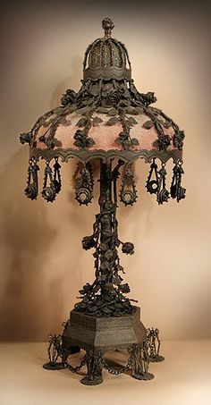 "Steampunk ""THE ROSE GARDEN"": A handmade iron table lamp with matching shade. Wire cages stand on the feet of the base, connected by chains. In the stem are dozens of thorned vines and roses. The shade has rose stems trailing down to its rim to oval shaped"