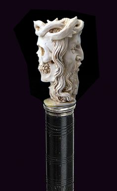"Ivory Skull and Christ with Crown ot Thorns. Circa 1885. A carved ivory skull morphs into the face of Christ, silver collar, exotic wood shaft and a metal ferrule (H. 2 ¼"" x 1 7/8"", OL. 25 ½"")"