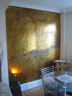 Wall by Emily Swift Jones. She began with a normal, painted wall, smoothed it out with joint compound, primed with shellac and then went to town. The steps included Dutch metal gold leaf, patinating the gold leaf, glazing with oil colours and varnishing for the top coat. At the end, she embedded tiny glitter flakes into the tacky varnish.