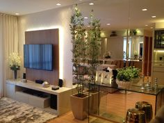 Boa noite queridos!! Sala tv com painel tv com iluminação indireta, ao lado aparador em vidro e parede toda em espelho!! O bambu completa a…