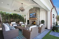 Chic covered patio with covered ceiling accented with a bronze sphere pendant illuminating a u shaped furniture arrangement composed of a wicker sofa and wicker chairs accented with navy trellis pillows facing a teak coffee table atop a green and blue striped outdoor rug facing a stone fireplace with flatscreen TV.