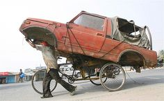 A man uses his cycle-rickshaw to take a truck body to a scrapyard in India.