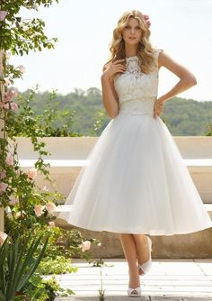 - Tea Length - Sweetheart neckline - Capped sleeve - Tulle Skirt - Mock button detail on back - Lace appliques on bodice