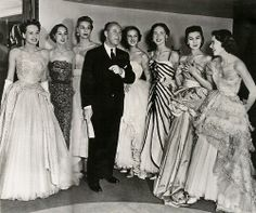 Christian Dior with models wearing his gowns, 1950.