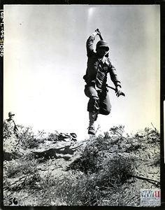 Greatest generation: Soldier jumping towards camera with Bolo knife/machete during training maneuvers wasting no time in rushing the enemy.  Image: U.S. Army Signal Corps photograph, Gift in Memory of Maurice T. White, from the collection of The National World War II Museum
